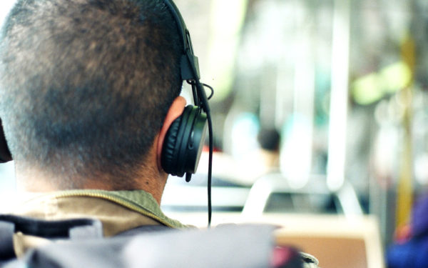 man on bus listening to podcast