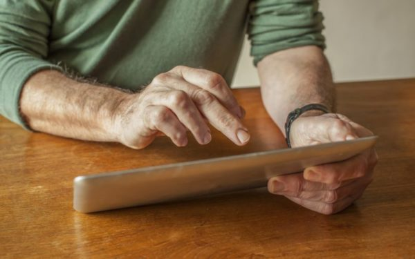 man using ipad - whole life insurance as an investment