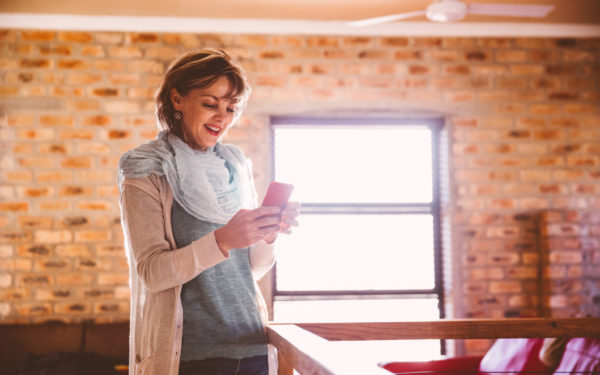 woman using phone - borrowing against life insurance