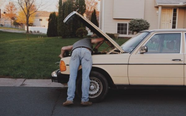 man under the hood of old car - how to buy a car with no credit car loan