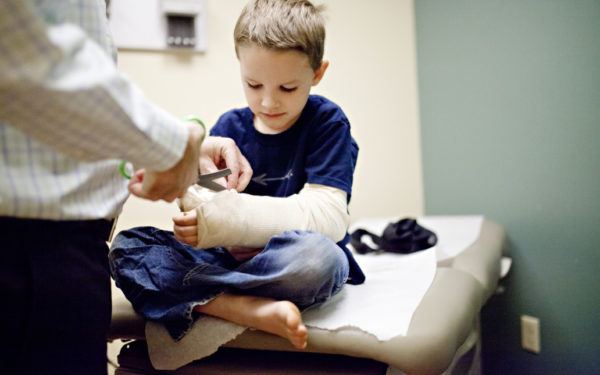 kid in doctor's office with cast - healthcare expenses