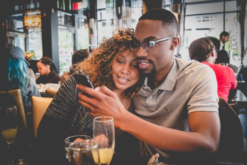 couple looking at phone - increase credit limit on credit cards