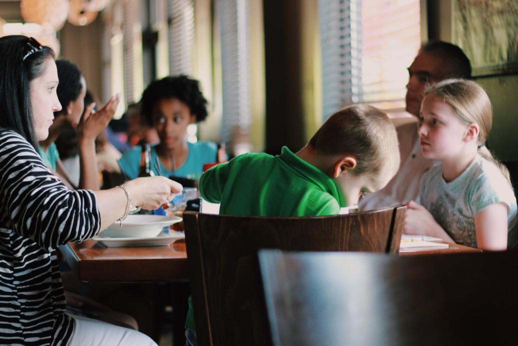 family eating dinner out at restaurant