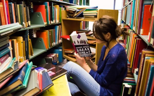 young woman reading in library - college