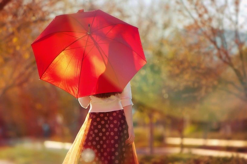 woman with red umbrella - planning for an extended leave of absence