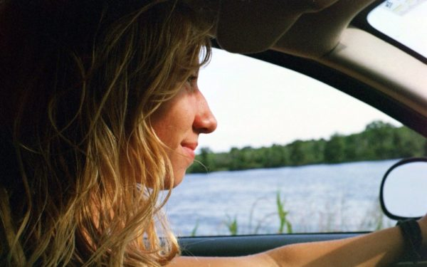 young woman driving - how to get a cheap rental car