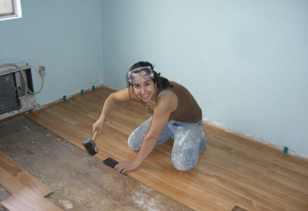 woman installing hardwood floors