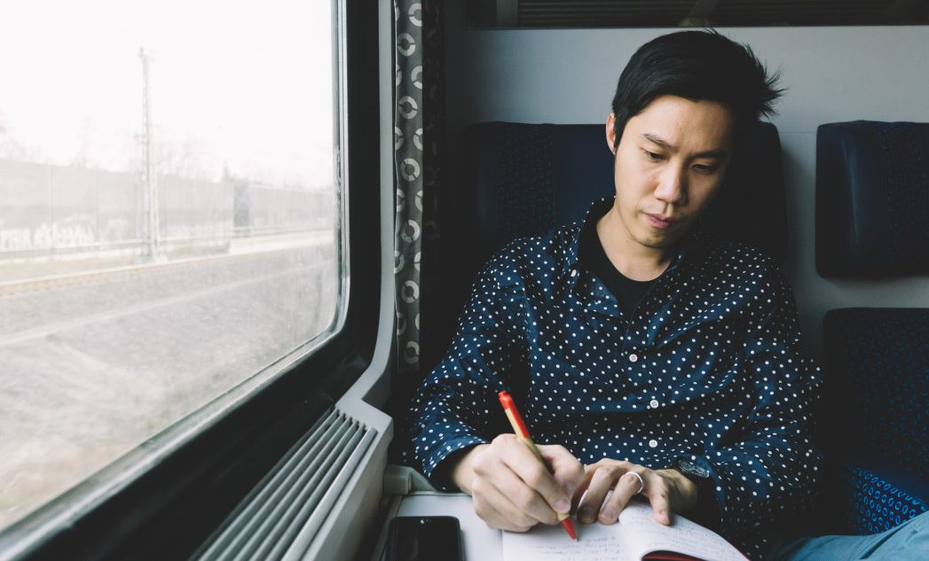 young man writing on train