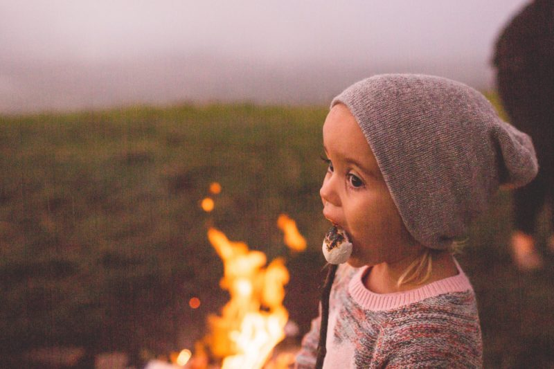 girl eating toasted marshmallow while camping with kids