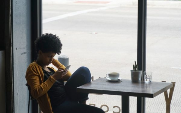 woman in cafe looking at credit score on phone