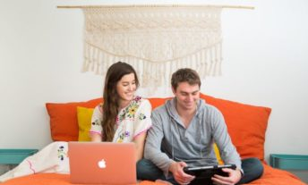 couple on a bed looking at laptop