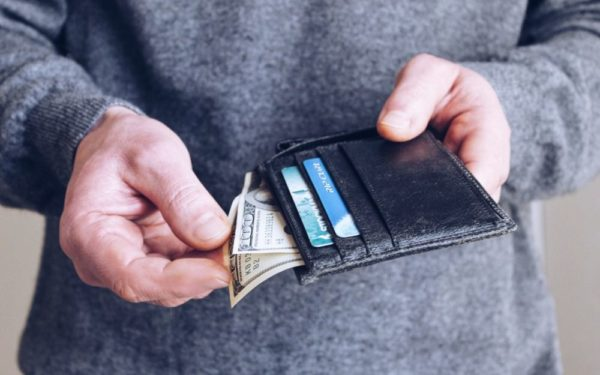 take the money - man pulling dollars out of wallet