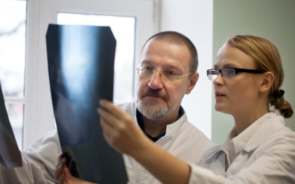 doctors examining x-rays - comparing health savings accounts