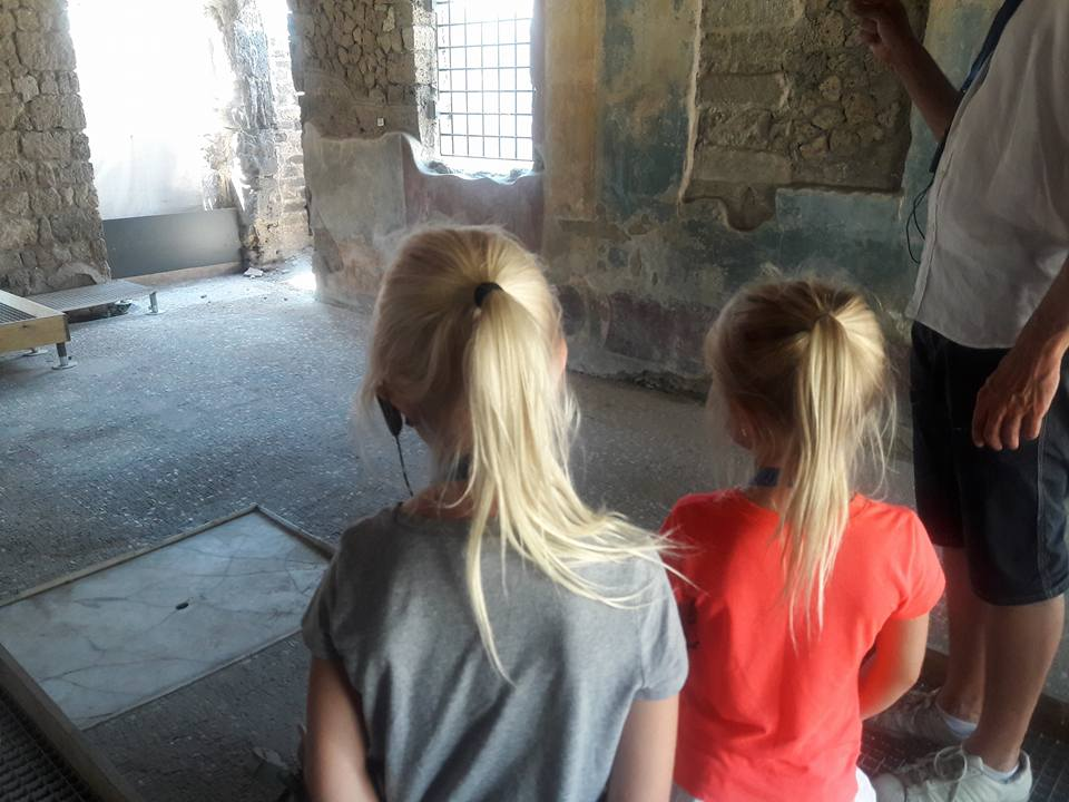 The kids exploring Pompeii, listening intently to their guide