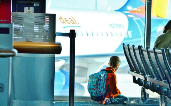 kid at airport plane in background - travel deals that aren't a deal