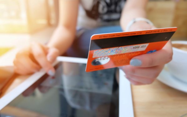 woman holding credit card with ipad - best secured credit cards