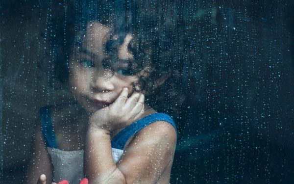 child looking out the window sadly on a rainy day