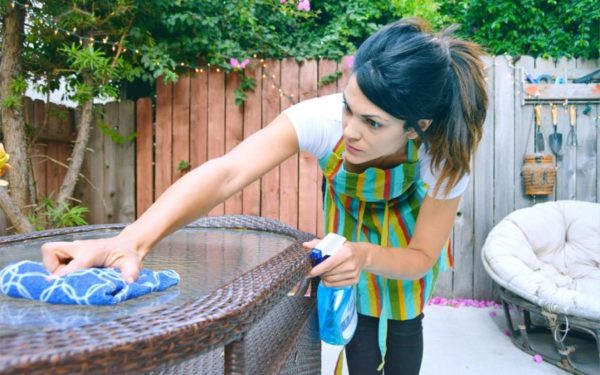 woman cleaning table with rag and windex