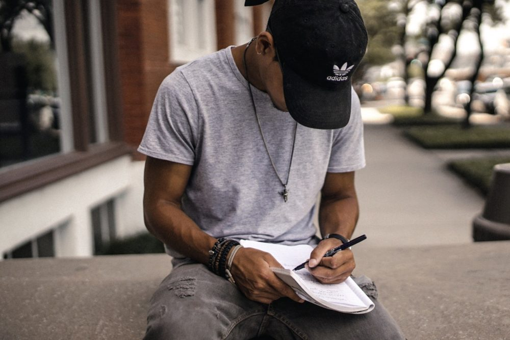 young man writing in notebook