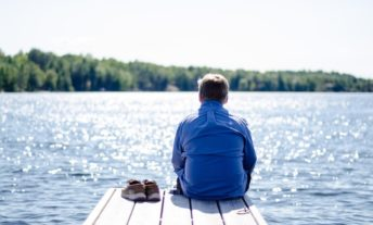 retirement mistakes - man sitting on dock by lake