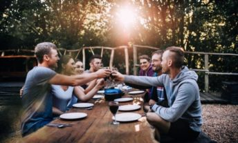 friends celebrating at dinner party outside in summer