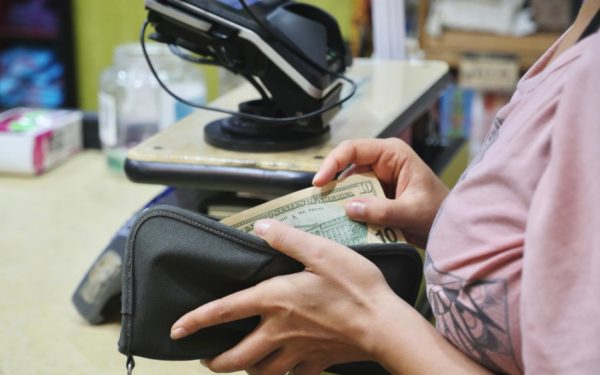 woman paying cashier at checkout counter - when to use your emergency fund
