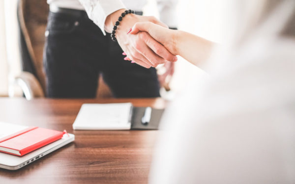 man and woman shaking hands over business deal
