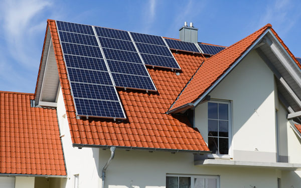 Image shows solar panels on top of a house.