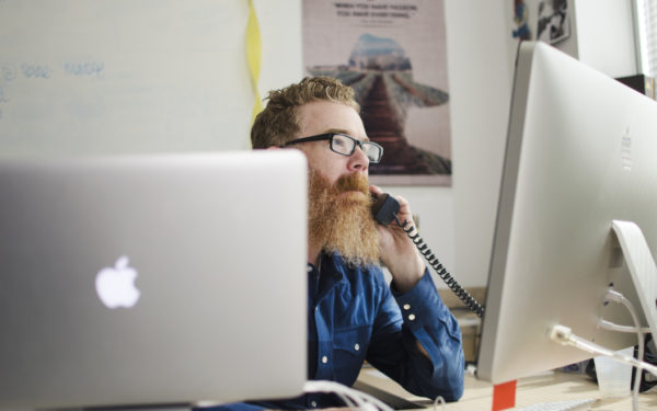 man on the phone at work - why employer stock is risky