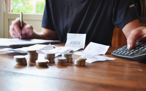 man budgeting with calculator