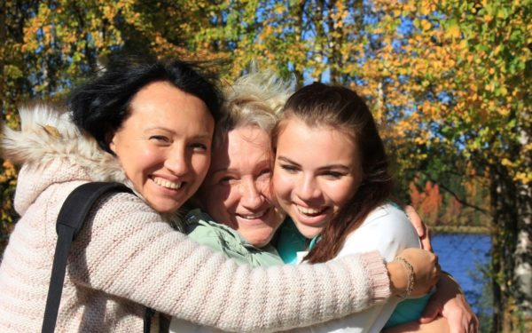 woman hugging her mom and daughter - the sandwich generation