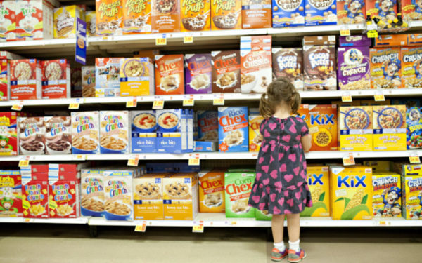 child looking at dozens of brands of cereals - the paradox of choice