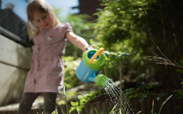 young girl watering plants in garden
