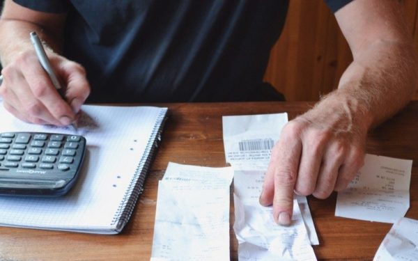 man budgeting with calculator and receipts