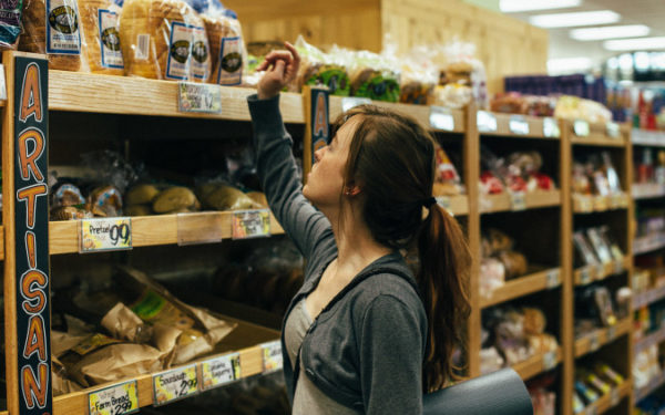 woman deciding which bread to buy at grocery store