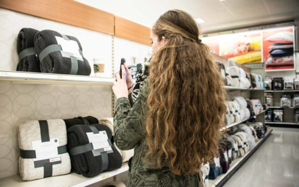 woman taking photo of item for sale in store - wishlist shopping