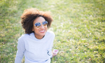 happy woman smiling in the sun - money mindset to get out of debt