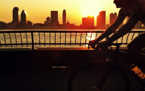 man bicycling by the river in new york