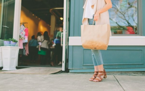 woman about to enter a store with shopping bag