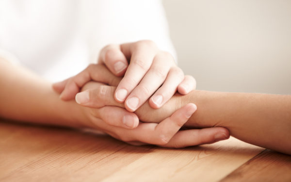 paying for cancer treatments holding hands
