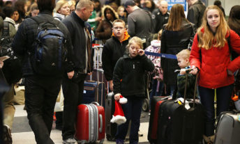 family waiting in airport with luggage - best travel insurance