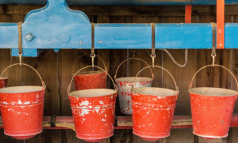 red buckets hanging from hooks - bucket budgeting with online bank sub-accounts