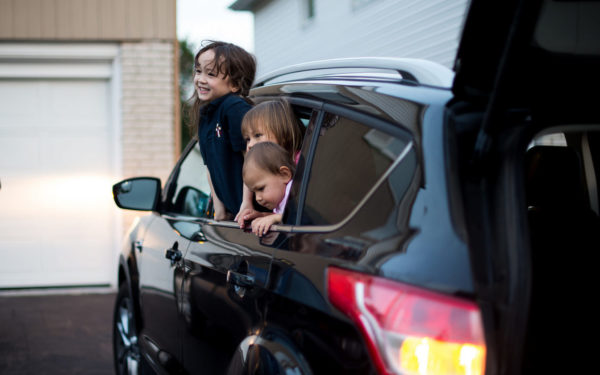 kids in a car in the driveway - how we make it as a one-car family in the suburbs