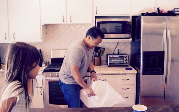 man changing trash bags in kitchen