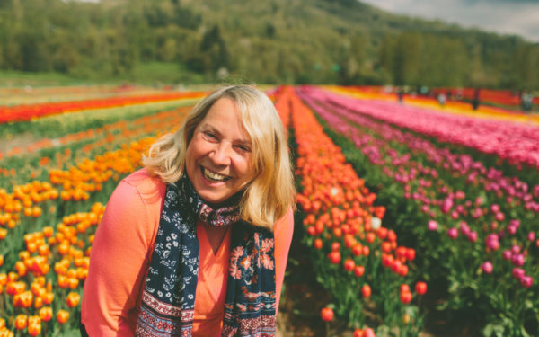 happy retired woman surrounded by tulips in spring smiling