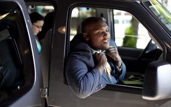 man adjusting bowtie in car - save money as a wedding guest