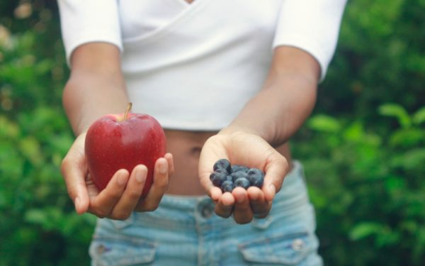 hands holding apple and blueberries