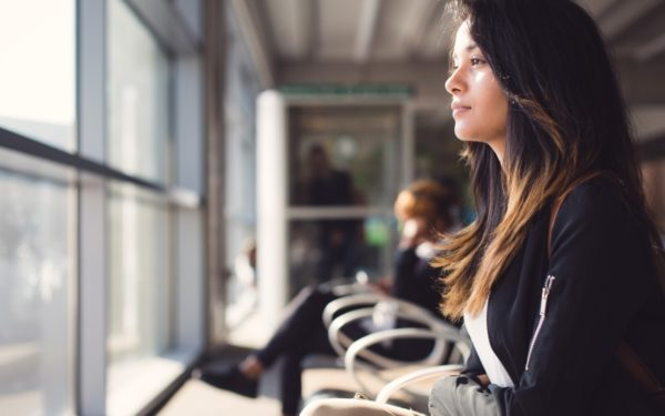 young woman at airport - jobs that pay you to travel