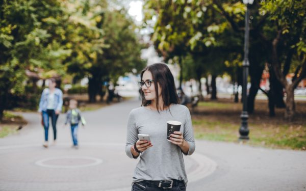 young woman walking in a city park