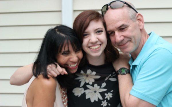 parents hugging adult daughter at home - multigenerational living